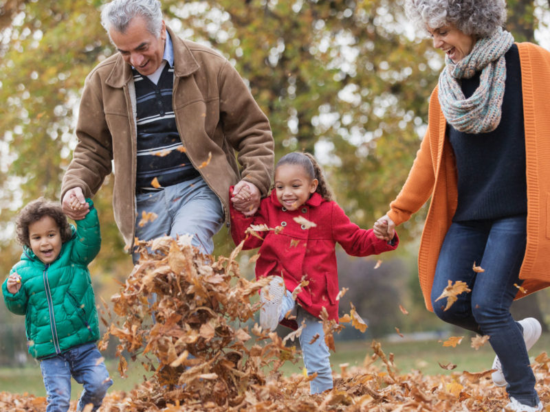 Grandparents and children playing in autumn leaves