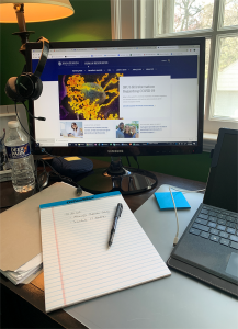 Desktop with water bottle, laptop, and notes